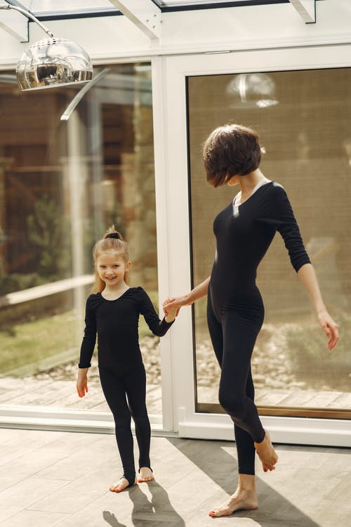 Woman and Little Girl in Black Long Sleeve Shirt and Black Pants Standing Beside Glass Wall