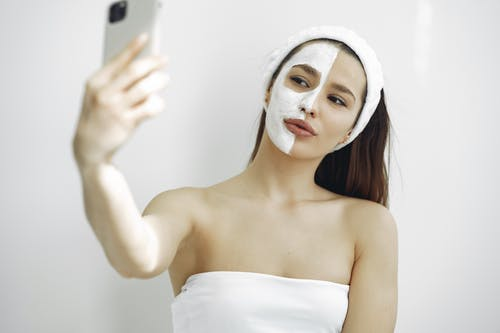 Woman in White Tube Top Holding Iphone