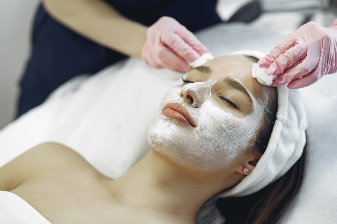 From above anonymous medical specialist in uniform and gloves wiping cream mask off face of relaxed woman during skincare procedure in modern studio