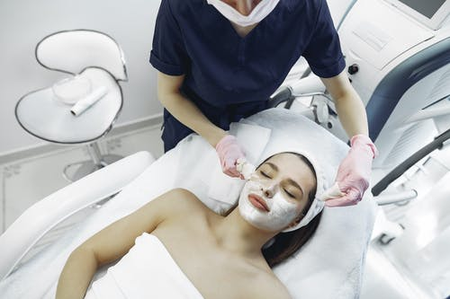 Crop female cosmetologist removing purifying mask from face of relaxed woman in contemporary clinic