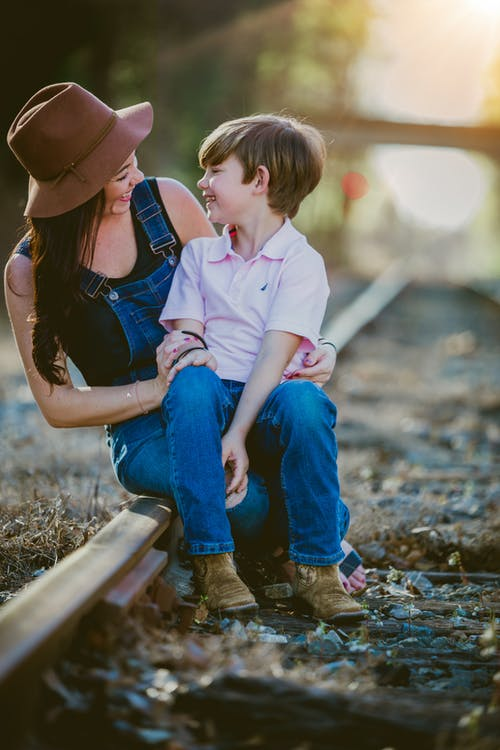 Mother and Son Seated on Railway Tracks