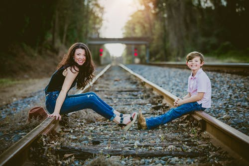 Woman In Black Top And Blue Denim Jeans With Her Child Sitting  On Railroad Tracks
