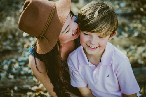 Woman In Brown Hat Smiling Beside Boy In Polo Shirt