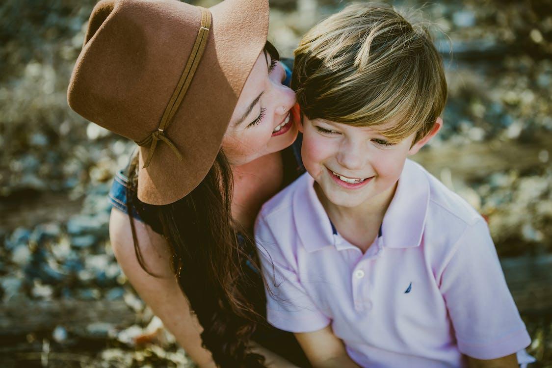 Vrouw In Bruine Hoed Glimlachen Naast Jongen In Polo Shirt