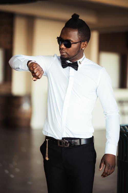 Man in White Dress Shirt and Black Pants Wearing Black Sunglasses