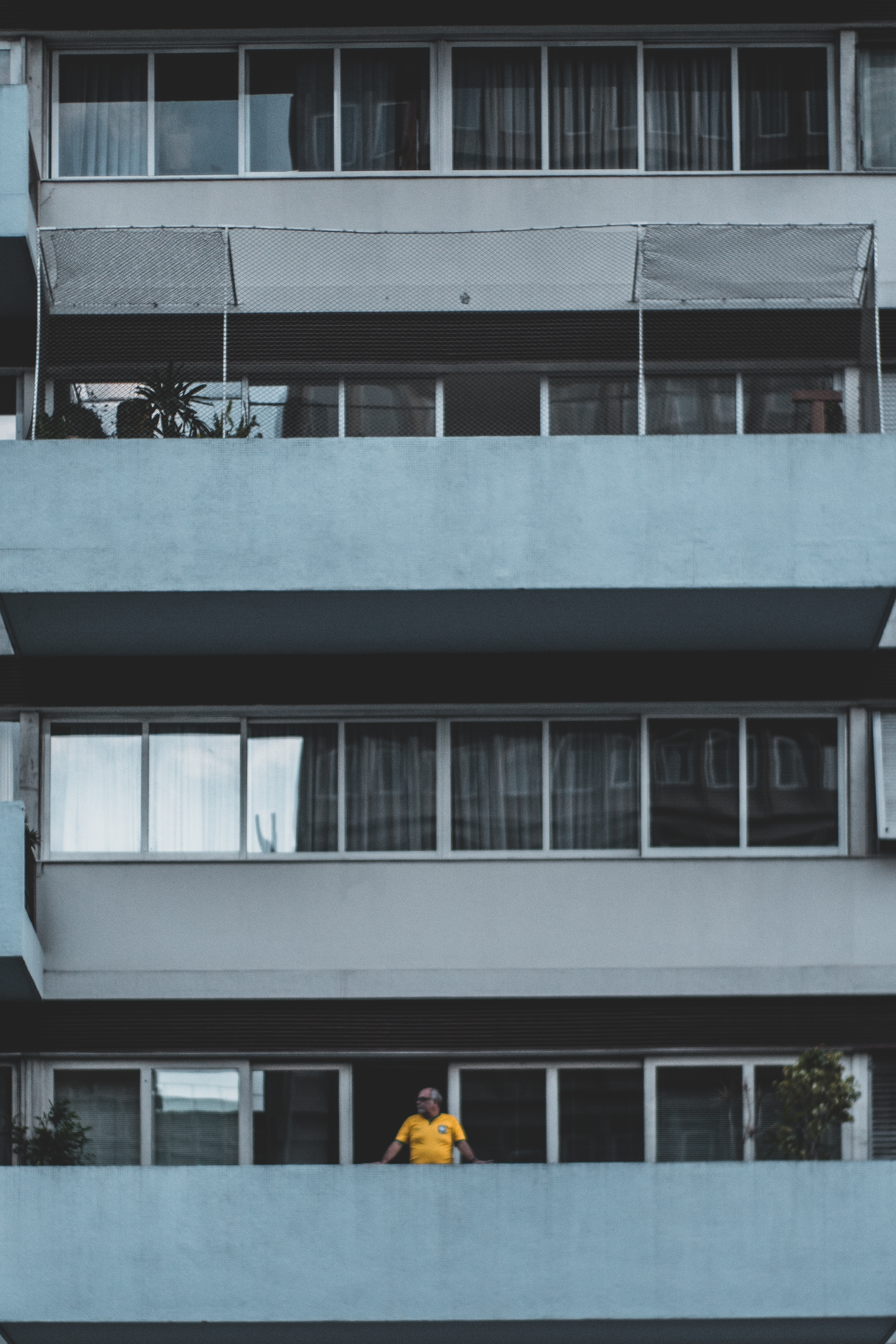 Person Leaning on Terrace of a Building