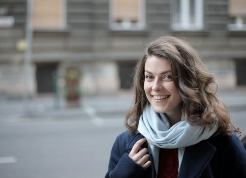 Woman in Blue Jacket and Scarf Smiling