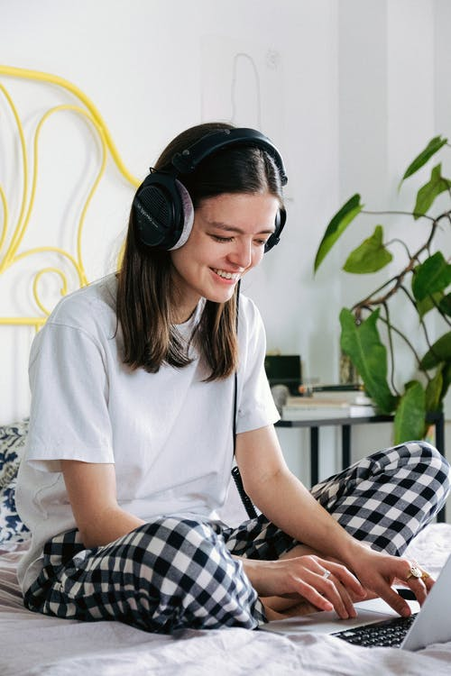 Woman In White Crew Neck T-shirt Wearing Black Headphones