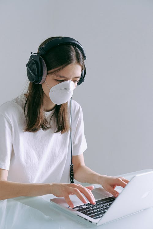 Woman In White Crew Neck T-shirt Wearing Headphones