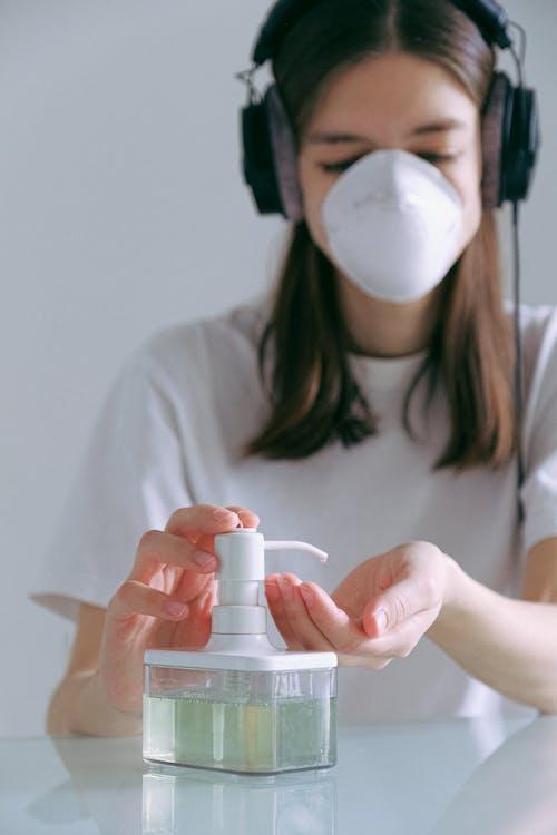 Woman In White Shirt Pumping Sanitizer