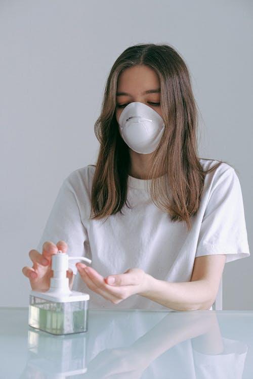 Woman In White Crew Neck T-shirt Pumping Sanitizer