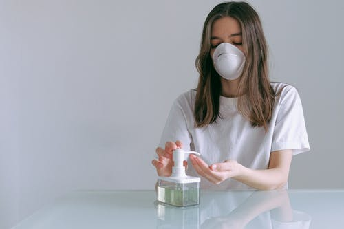 Woman In White Shirt Pumping Sanitizer