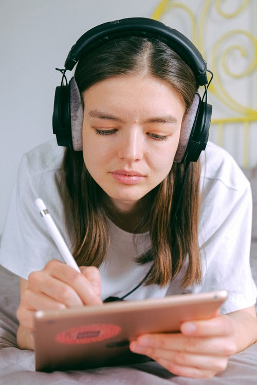 Woman In White Shirt Wearing Black Headphones
