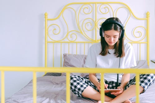 Woman In White Shirt Wearing Black Headphones Sitting On Bed