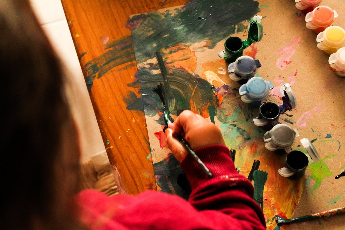 Person Painting on Brown Wooden Table