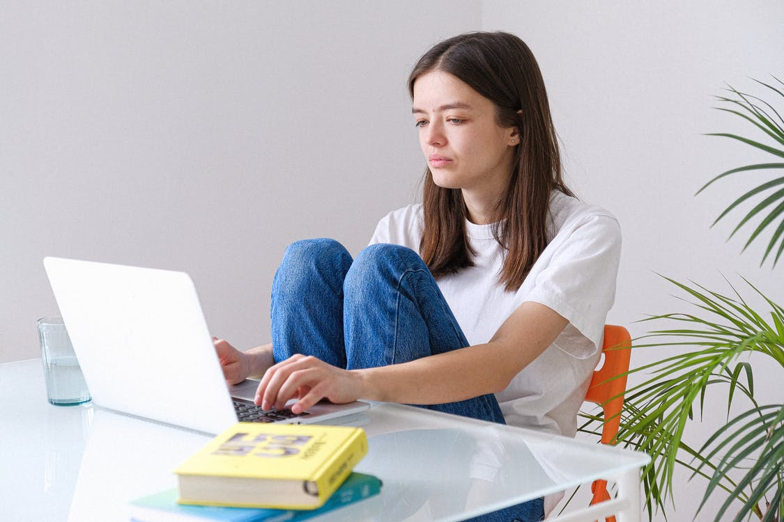 Woman in White Crew Neck T-shirt and Blue Denim Jeans Working on a Laptop