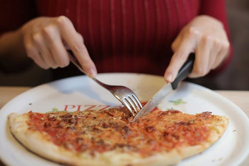 Person Holding Stainless Steel Fork and Knife Slicing Pizza