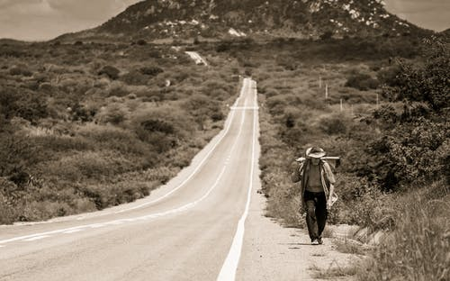 Grayscale Photo of Man Walking on Road