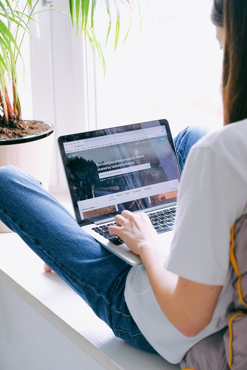 Person in White T-shirt and Blue Denim Jeans Using Laptop