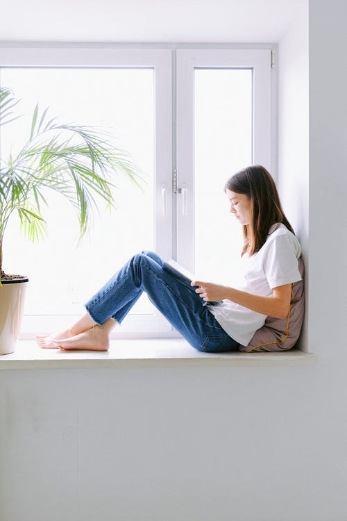 Woman In White Shirt And Blue Denim Jeans Sitting By The Window