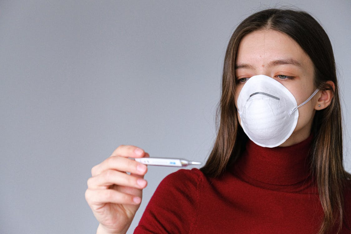 Woman in Face Mask Checking Thermometer