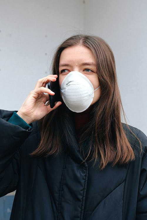 Woman in Face Mask Using Smartphone