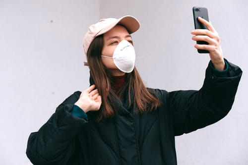 Woman in Face Mask Taking Selfie