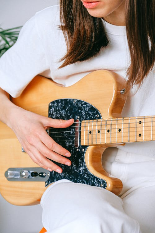 Woman in White Crew Neck T shirt Playing Brown and Black Electric Guitar