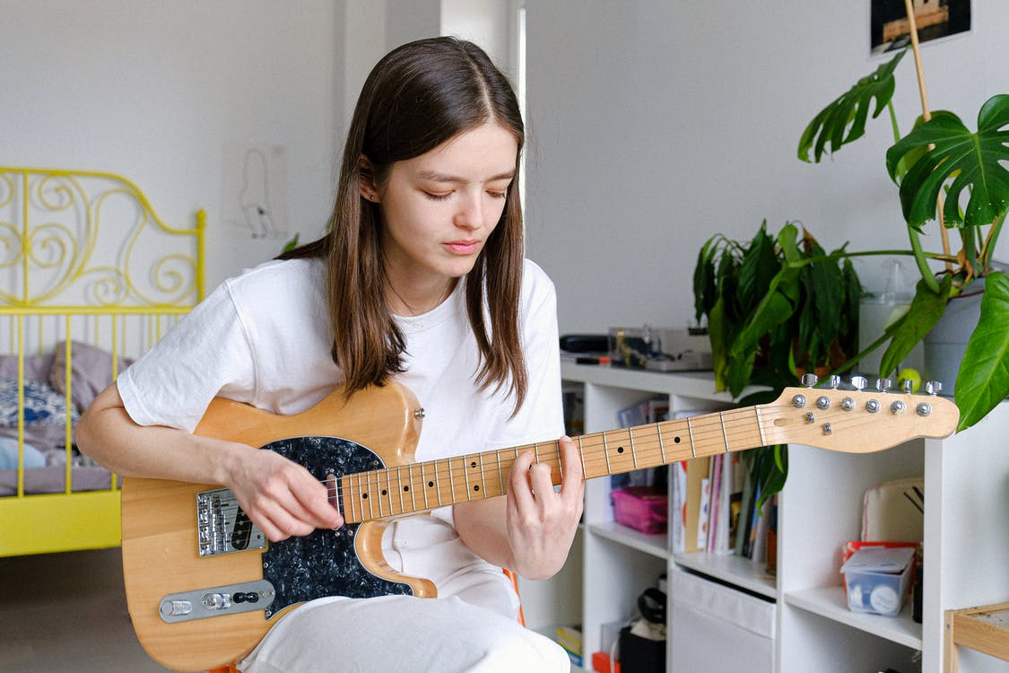 Woman In White Crew Neck T-shirt Playing Brown Electric Guitar