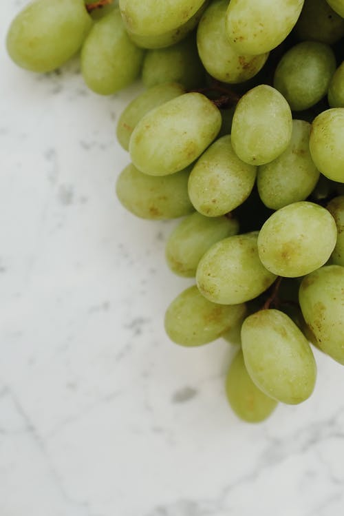 Green Grapes on White Table