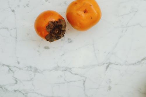 2 Orange Round Fruits on White Surface