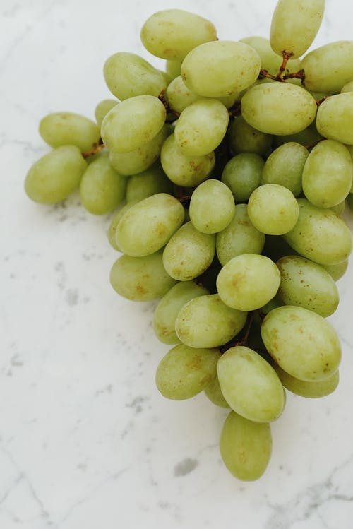 Green Round Fruits on White Surface