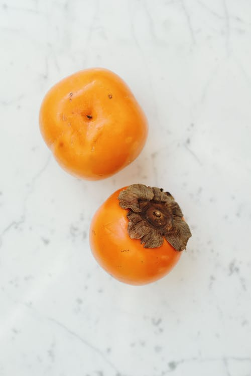 Persimmons on White Surface