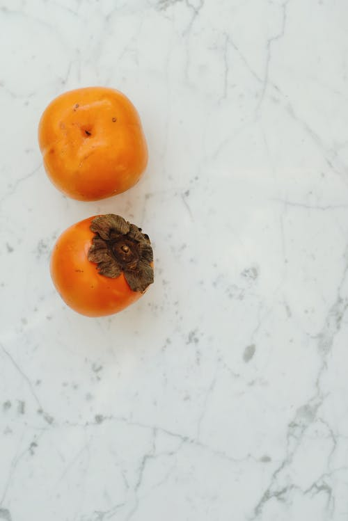 Persimmon on a White Surface