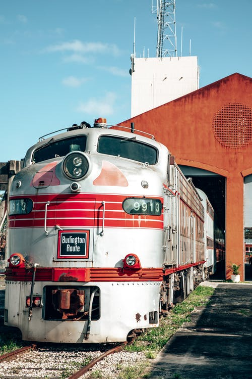 Red and White Train on Rail Tracks