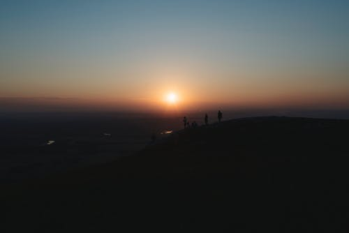 Silhouette Of People On Hill During Sunset