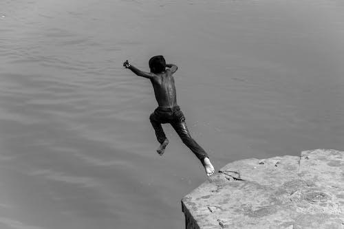 Man in Black Shorts Jumping on Rock