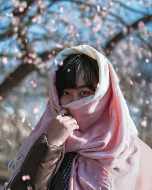 Woman Covering Her Face With White and Pink Scarf