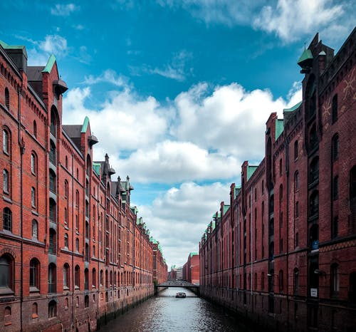 Brown Concrete Buildings Beside River Under Blue Sky