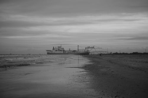 Grayscale Photo of Ship on Shore