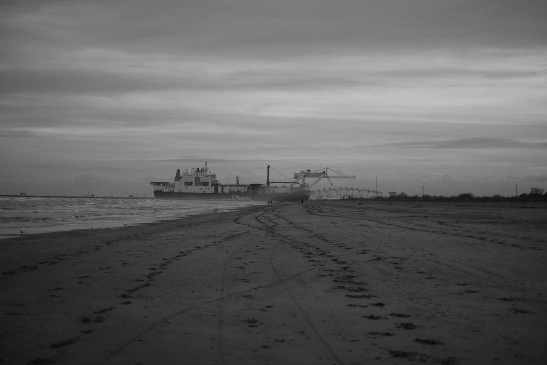 Grayscale Photo of Beach With Ship on the Sea
