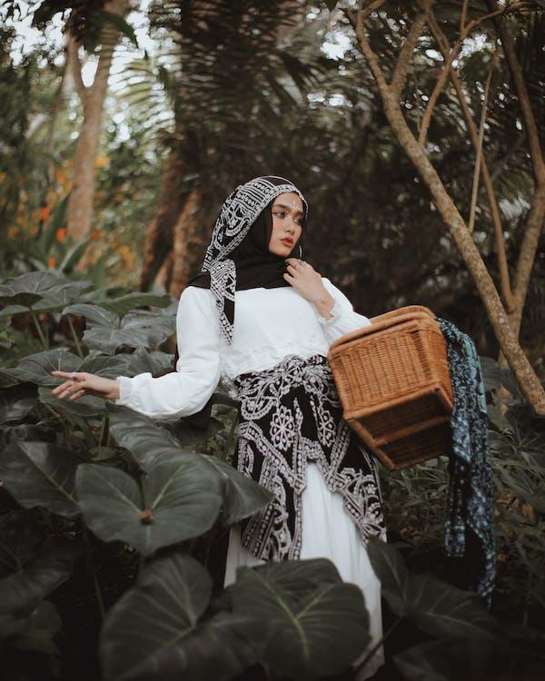 Woman in White Long Sleeve Dress Bringing Brown Basket