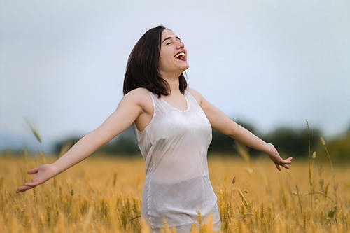 Woman in White Tank Top Standing on Brown Grass Field