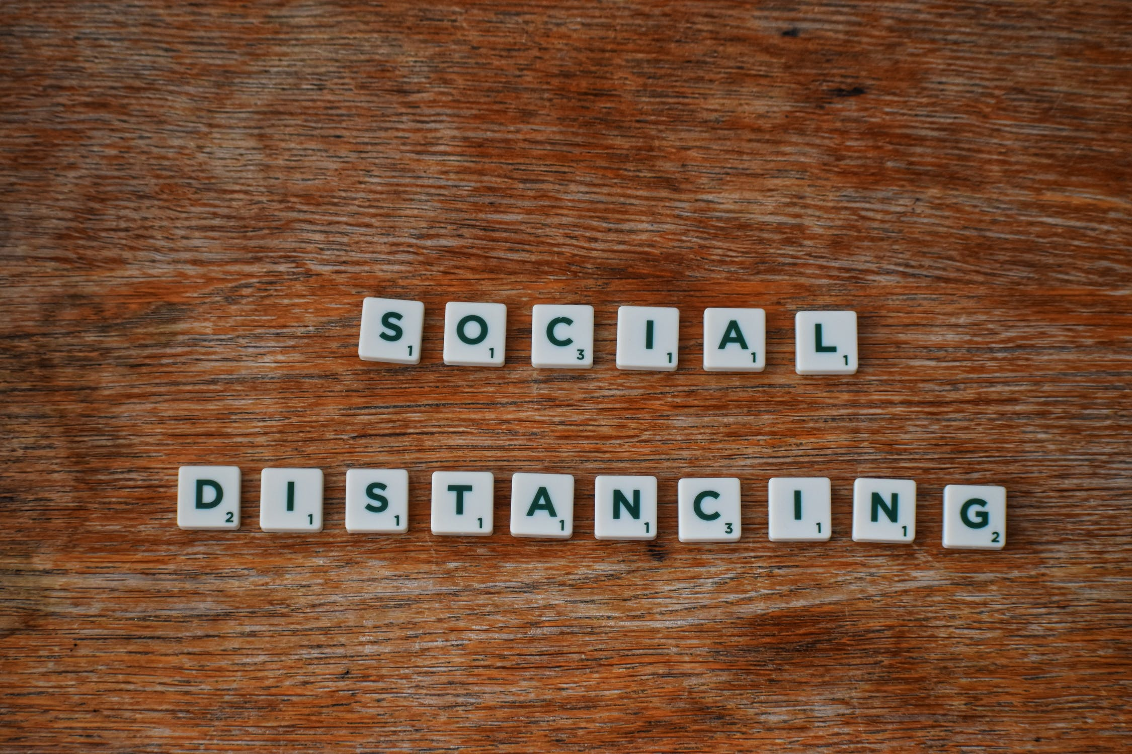 "Scrabble letters spell out ""Social Distancing"" on a wooden table"