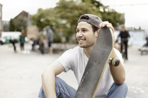 Man in White Crew Neck T-shirt and Blue Denim Jeans Holding Skateboard