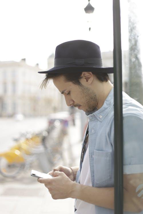 Man in Blue Denim Jacket and Black Hat Holding Smartphone
