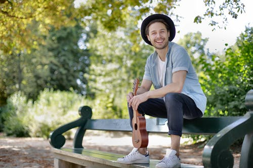Man in Blue Crew Neck T-shirt and Black Pants Sitting on Wooden Bench