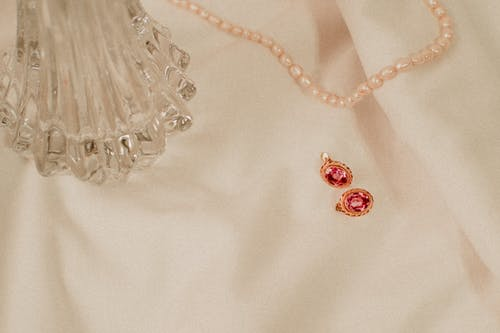 Pearl Necklace And Pair of Earrings on White Textile