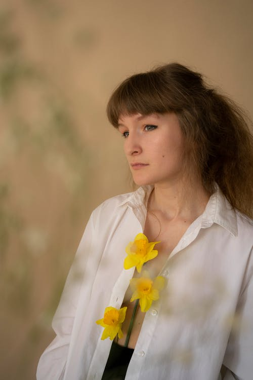 Woman in White Button Up Shirt With Yellow Flower on Her Chest