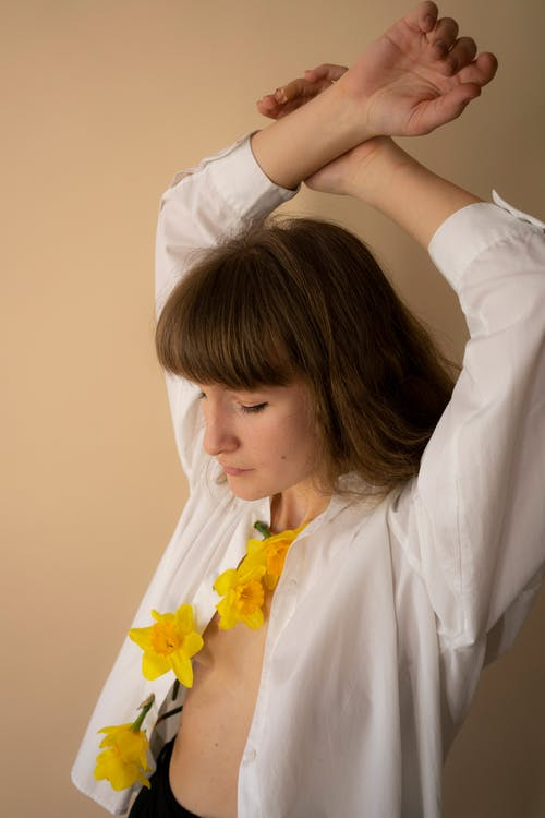 Woman in White Dress Shirt Holding Yellow Flowers